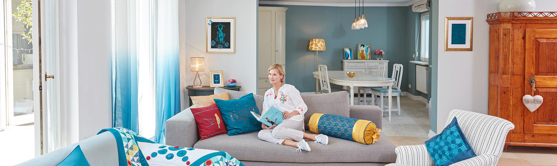 Wohnzimmer mit Quilt, bestickten Kissen und Frau, die ein Buch liest