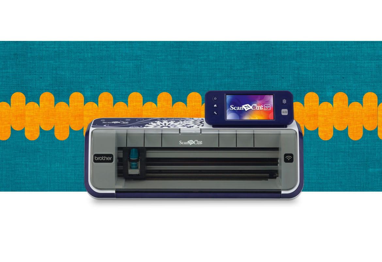 CM900 scanncut machine on a dark blue and orange background