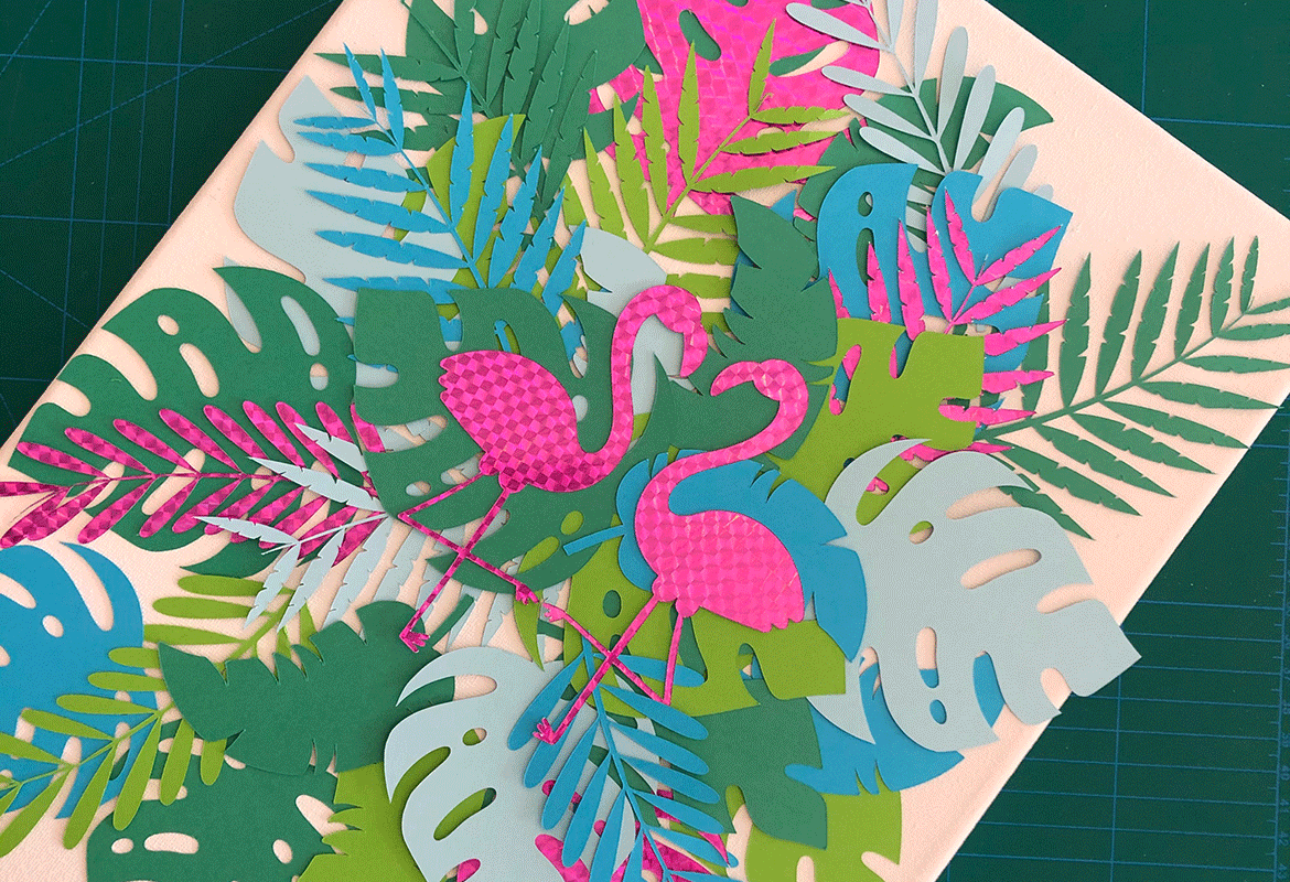 Two pink paper flamingos on colourful large green paper leaves