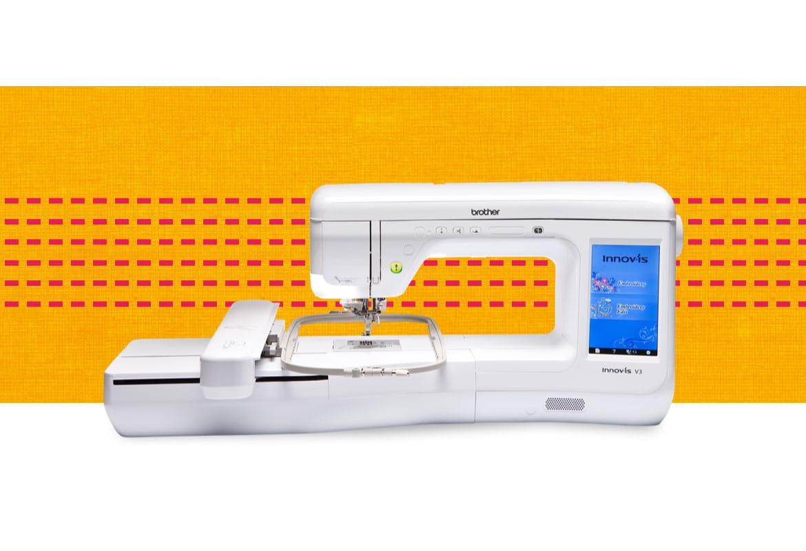 V3 embroidery machine on an orange and red pattern background