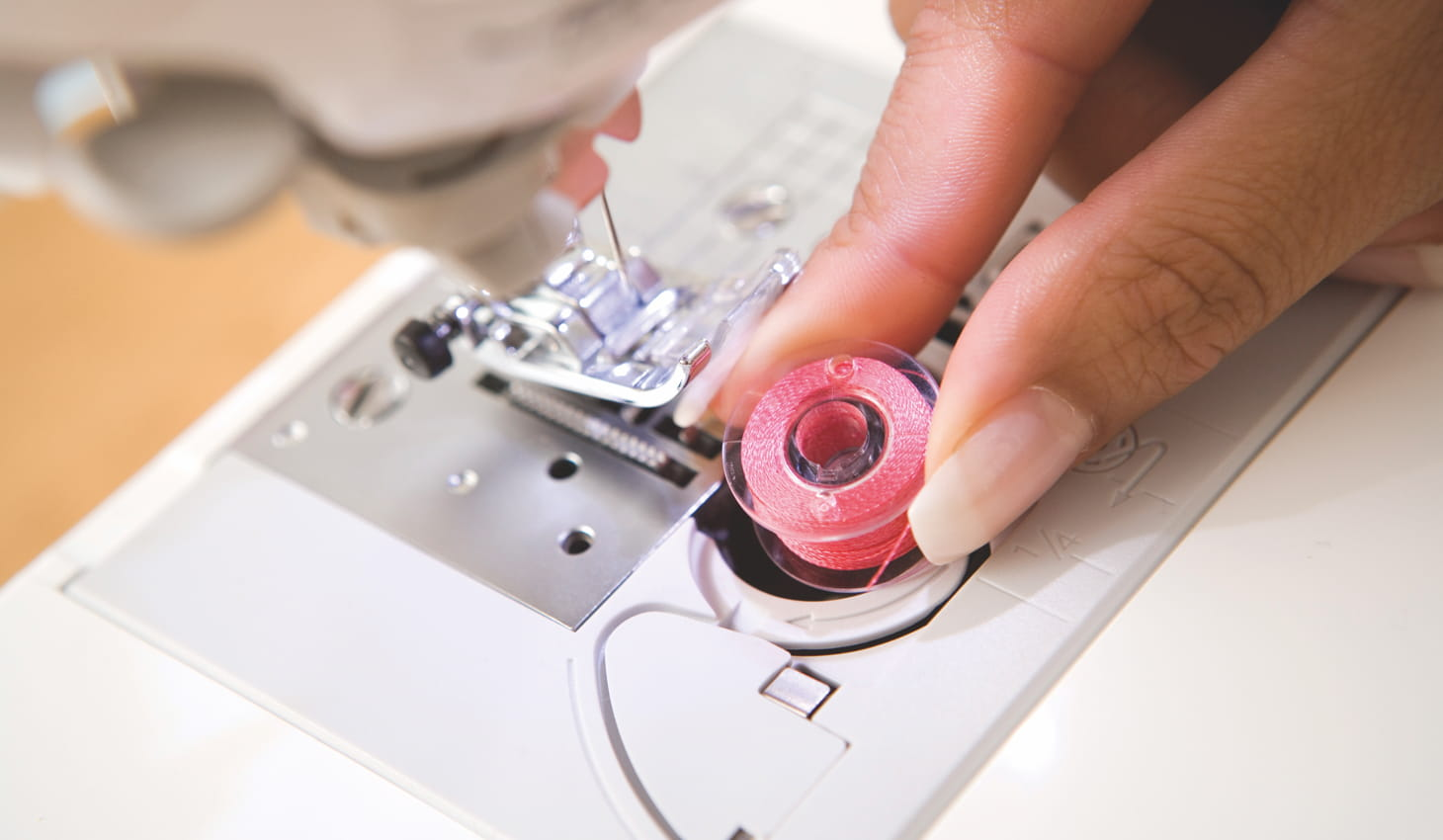 someone replacing the bobbin on a sewing machine
