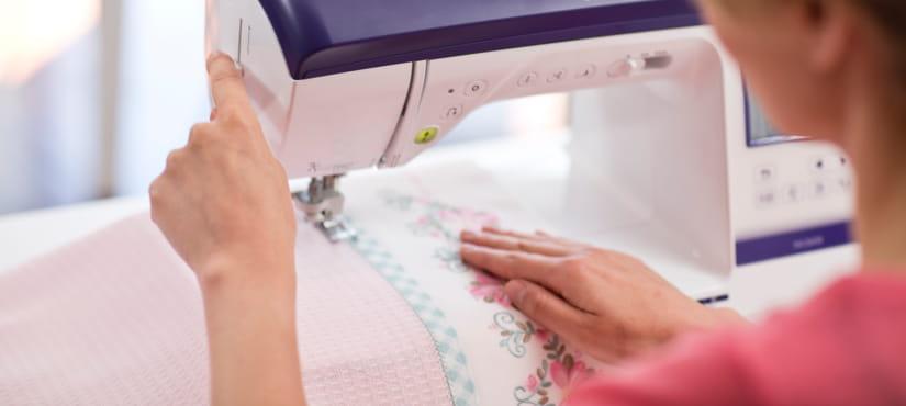 Una donna cuce del materiale con una macchina per cucire